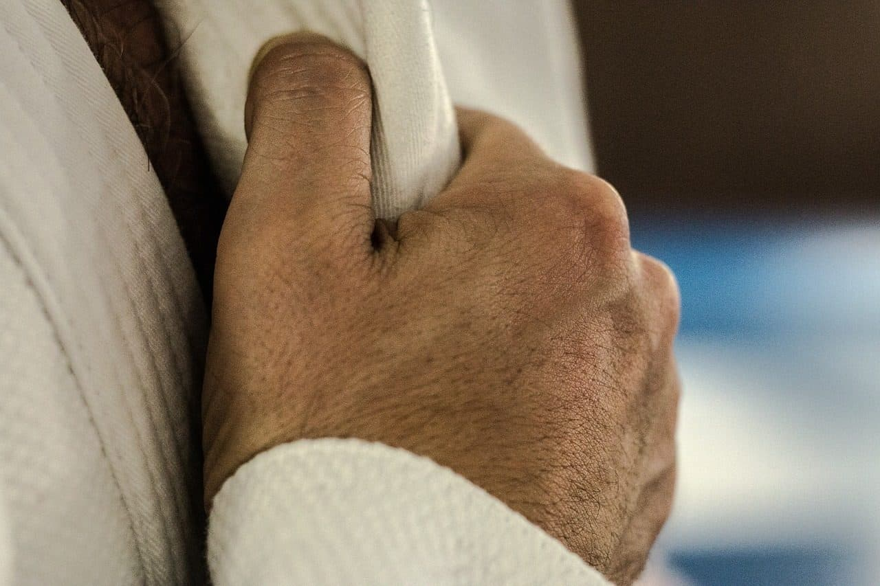 A hand taking a grip on a new BJJ gi